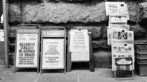 Black and white news stands on street.