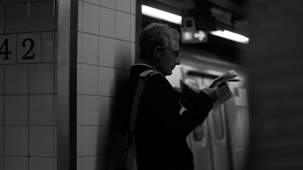 black and white picture of man reading on the underground alone