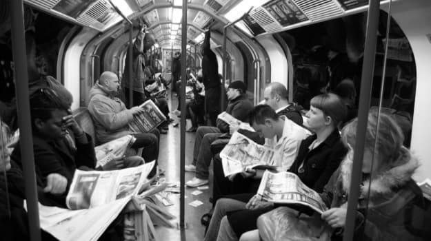 Black and white picture of people reading newspapers on the tube