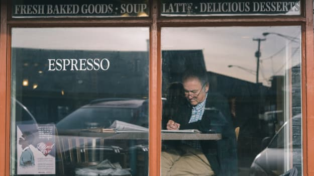 old man reading newspaper in coffee shop window