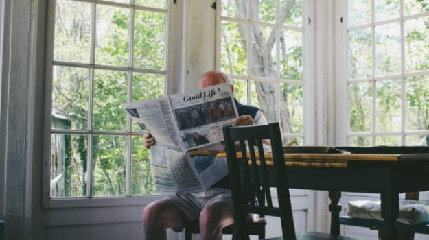 Picture of old man reading newspaper in living room
